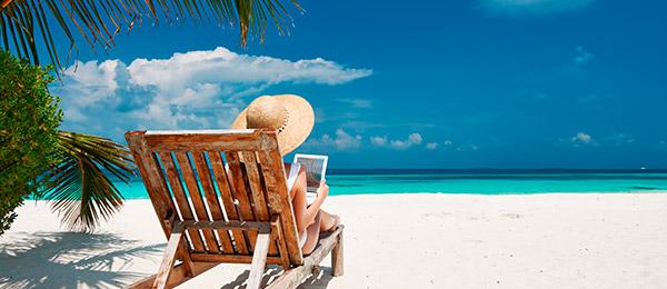 Pessoa lendo catálogo na praia